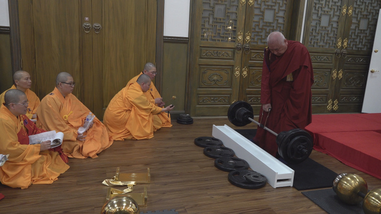 After Buddhist disciples who signed up for the Exam all failed to lift the Vajra Pestle with the starting weight of 180 pounds, Kaichu Jiaozun, who is almost 90 years old, surprisingly lifted the 180-pound Pestle, and was further able to lift the Pestle with the weight increased to 200 pounds and hold it for seven seconds to fulfil the rules. The congregation was amazed by such wondrous physical power. Buddhist nuns in the photo were each carrying out their responsibilities in proctoring the Exam and recording the results.